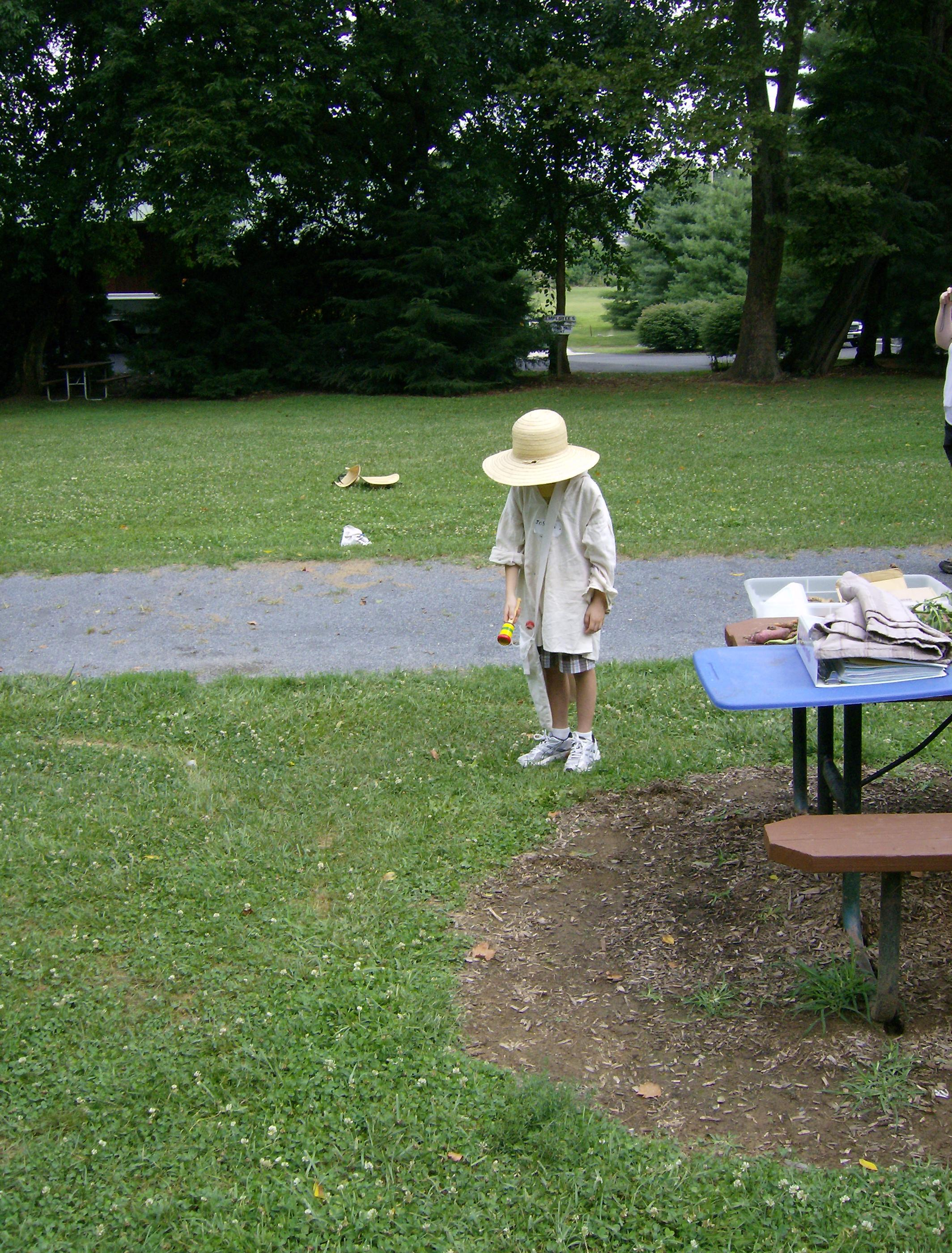Child standing next to picnic table